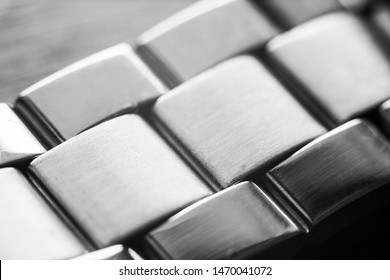 Macro closeup on links of stainless steel watch metal band - monochrome image
