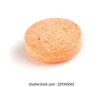 Macro closeup of orange vitamin c chewable tablet isolated on white