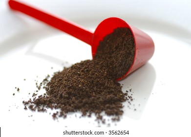 Macro closeup of a red conical coffee scoop with ground coffee poured onto a white plate
