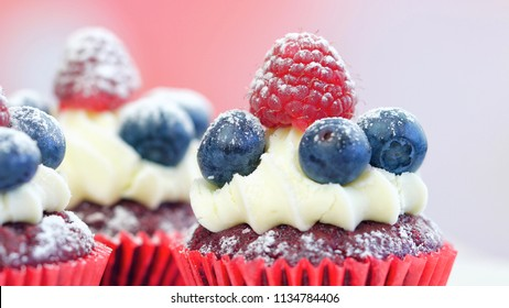 Macro closeup of red velvet cupcakes decorated with fruit and dusting with confectionery sugar.