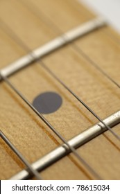 Macro close-up shot of the maple fretboard of an electric guitar.