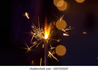 macro closeup of a single sparkler glowing and shooting sparks at night