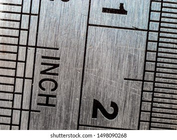 Macro close-up of a stainless steel ruler with british and metric system measuring scales: Inches and millimeters.