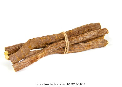 Macro closeup of a traditional sweet heap pile of Liquorice licorice wooden wood roots sticks isolated on white
