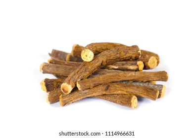 Macro closeup of a traditional sweet heap pile of Liquorice licorice wooden wood roots sticks spice isolated on white