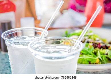 Macro closeup of two plastic cups with ice cubes and water and condensation on table with straws by green salad in restaurant