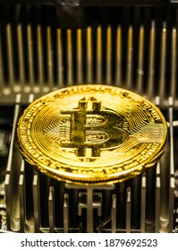 Macro close-up view bitcoin cryptocurrency  minted symbolic coin. It placed on personal computer mainboard microchip's radiator.