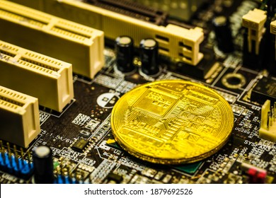 Macro close-up view bitcoin cryptocurrency  minted symbolic coin. It placed on personal computer mainboard microchip, with lots of numbers, capacitors and other electronic elements near it.