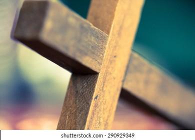 A macro closeup of a wooden Christian cross laying at an angle.
