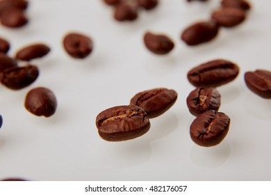 macro of coffee beans on a white background with reflections
