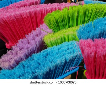 Macro of colorful street brooms at a market in pink, blue and green