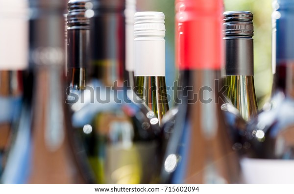 Macro crop on top of red and white wine bottles closed with metal caps. Close up background with shallow depth of field.