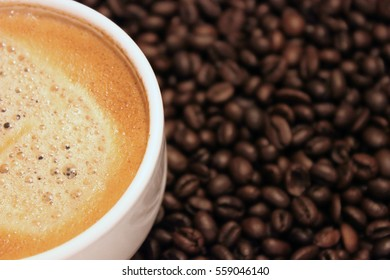 A macro cup of Cappuccino is a coffee beans