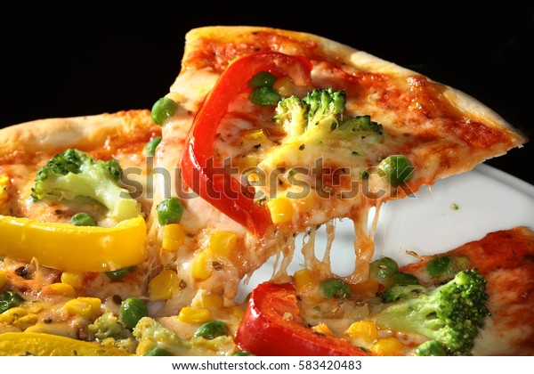 macro delicious pizza with bell pepper, broccoli and peas on a dark background studio