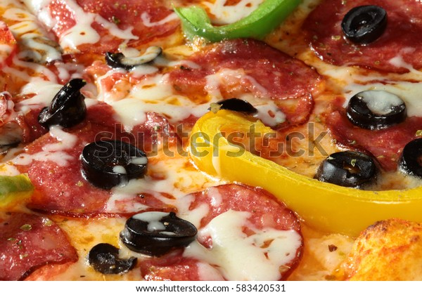 macro delicious pizza with bell peppers, salami and olives on a dark background studio