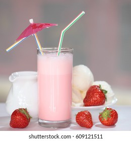 macro delicious strawberry milkshake in a glass on a light blurred background
