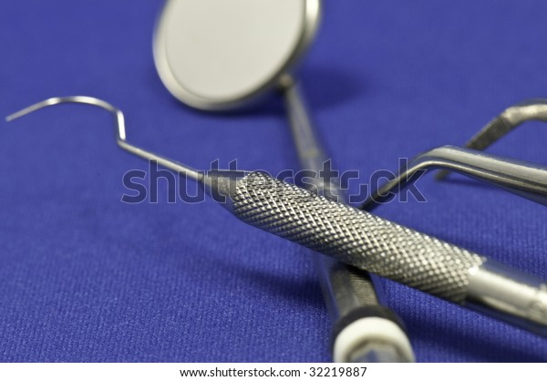 Macro of the dentist instruments on a blue background.