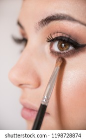 Macro detail of caucasian model brown almond eyes during make-up session. The make-up artist is applying a brown eye shadow with the brush.  The model has white, clean complexion.