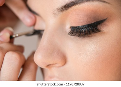 Macro detail of caucasian model false eyelashes during make-up session. The make-up artist is applying a black eyeliner with the brush. The model has white, clean complexion.