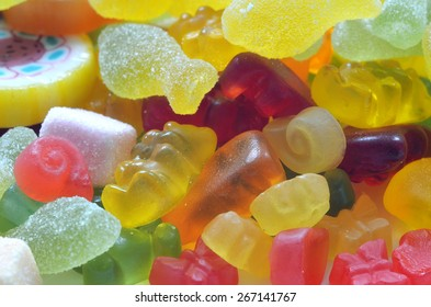 Macro detail of lollipop, gummy bears and sour candy on colored smarties background