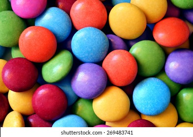 Macro detail of pile of colored smarties background. Close-up of candies texture.