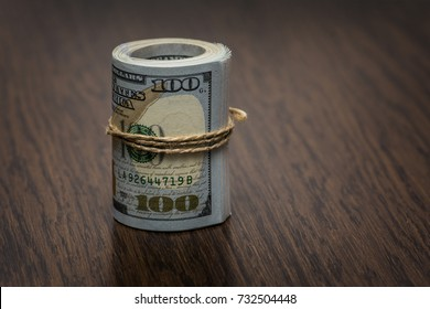 Macro detail of a roll of American currency (USD, American dollars) with 100 and 50 dollars bank notes on the outside as a symbol of plenty of money on the wooden background. Money on the table