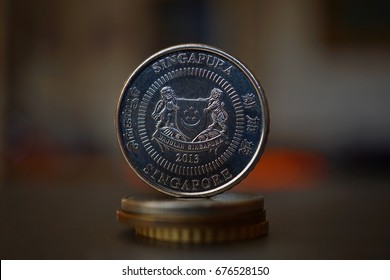 Macro detail of a Singaporean coin (Singapore dollar, SGD) on the top of column created of coins with a positive colorful warm background