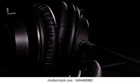 Macro details of black leather headphones on black background