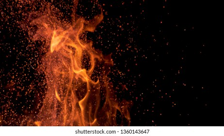 MACRO, DOF: Cinematic shot of blazing flames flickering in the darkness of the night. Colorful flames flickering and sparkles flying out of a campfire in pitch black wilderness. Orange fire blazing.