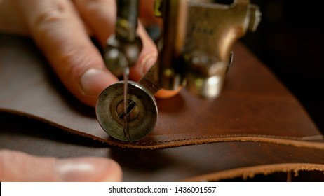 MACRO, DOF: Cobbler sewing together a pair of beautiful brown shoes with sewing machine. Sewing machine creating a seam along the upper part of a brown leather shoe. Traditional shoemaking process.