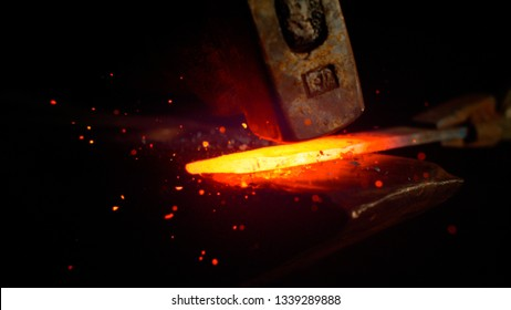 MACRO, DOF: Red hot piece of metal is being held by iron tongs and struck by a big hammer. Glowing particles flying away from a knife blade being manufactured by experienced bladesmith. Sparks flying.