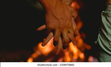 MACRO, DOF: Unrecognizable young man and woman holding hands over the campfire. Carefree tourists camping in the wilderness playfully interlocking their fingers while observing the blazing fire.