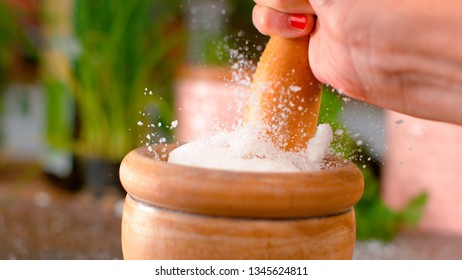MACRO, DOF: White grains of sea salt fly up in air out of mortar upon impact with a wooden pestle. Unrecognizable female chef strikes the clump of coarse rock salt while gripping a round wooden stick.