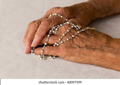 macro of elderly caucasian hands holding a silver rosary