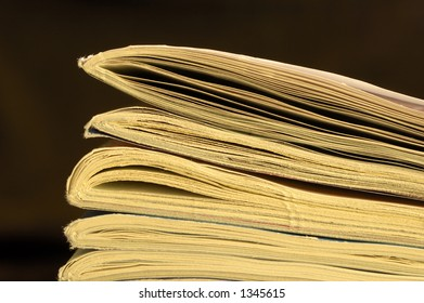 Macro of the end of a pile of old, yellowing magazines, set against a black background, with space for text.