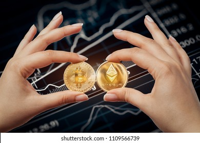 macro female hands holding bitcoin and ethereum side by side in front of stock market chart
