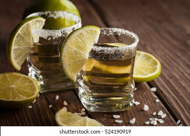Macro focus photo of shots of golden Mexican tequila with lime and salt on wooden background. Alcoholic drink concept.
