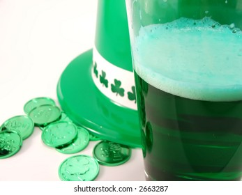 macro of green beer with hat and coins in background