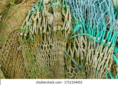 Macro of a green blue trawl fishing net with thick tow ropes on the fisher's quay; fishing harbor; Nieuwpoort, Belgium, Europe