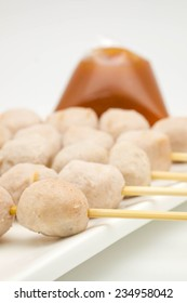 Macro of grilled or barbecued pork ball as a delicious appetizer with spicy sauce on white plate for food background