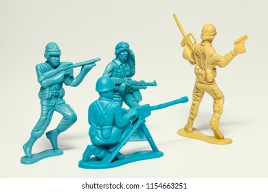 macro group of plastic toy soldiers with guns taking prisoner the enemy soldier