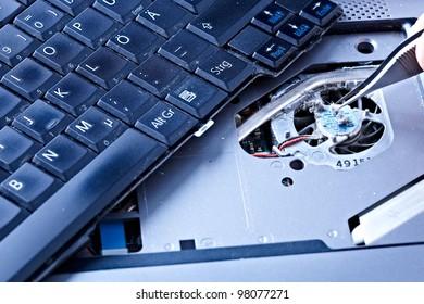 macro of a hand holding tweezers on a laptop fan