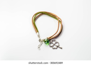 Macro of handmade bracelet made with colorful leather straps, clover pendant and crystal glass isolated on white background.