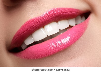 Macro happy woman's smile with healthy white teeth, bright pink .lips make-up. Stomatology and beauty care. Woman smiling with great teeth. Cheerful female smile with fresh clear skin