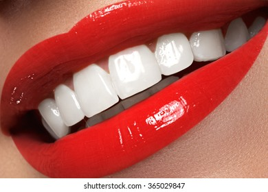 Macro happy woman's smile with healthy white teeth, bright red lips make-up. Stomatology and beauty care. Woman smiling with great teeth. Cheerful female smile with fresh clear skin