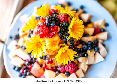 Macro high angle closeup of colorful vibrant bowl of ice cream topped with blue blueberries bilberries, calendula yellow whole flower petals, raspberries dessert apple fruit salad