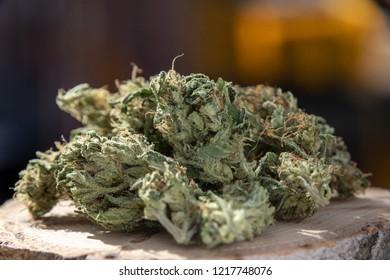 Macro Homegrown Marijuana Buds. Close up Cannabis Flowers on Wood Plate with Copy Space.