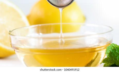 Macro image of bee honey dripping from metal spoon in glass jar
