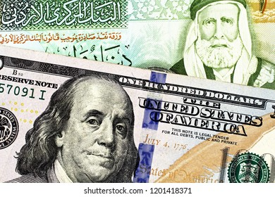 A macro image of a blue American one hundred dollar bill with a Jordanian one dinar bill