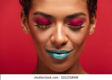 Macro image of charming african american woman being fashionable and trendy wearing colorful cosmetics, posing with closed eyes, over red wall
